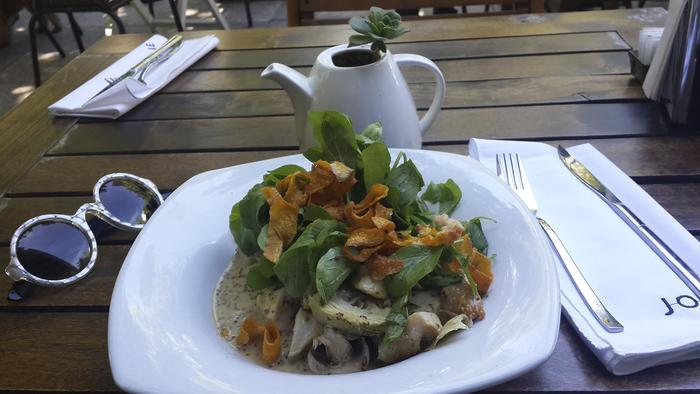 Ensalada de verdes y champignon sobre mesa de madera