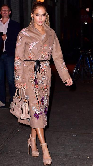 Jennifer Lopez caminando con gabardina floreada
