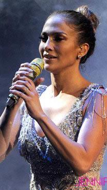 Jennifer López cantando, con micrófono en mano