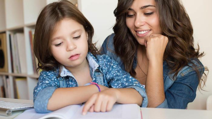 Joven ayudando a una niña a leer