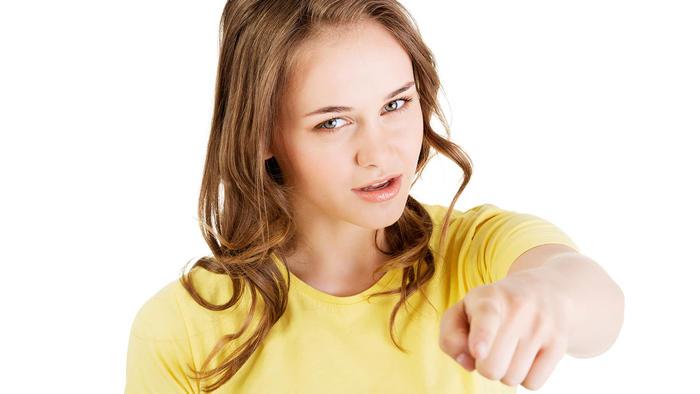 Joven de camiseta amarilla apuntando con el dedo