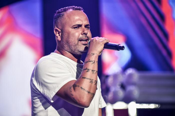 Juan Magan cantando y sosteniendo el micrófonocon su brazo tatuado en los ensayos de Premios Billboard 2015