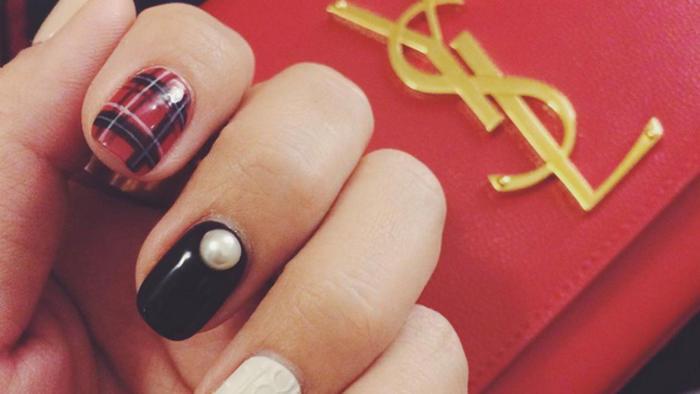 Uñas de colores junto a bolsa roja de YSL