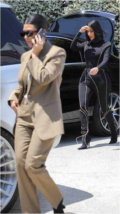 Kourtney Kardashian con traje café y Kim Kardashian