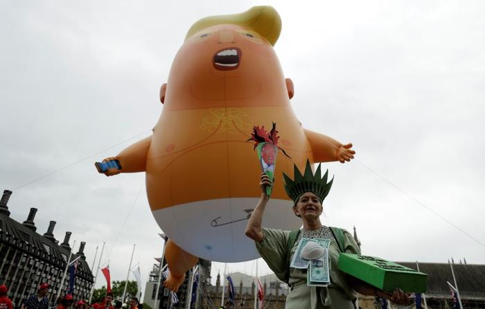 Una mujer disfrazada de la Estatua de la Libertad junto al globo del Trump bebé en la manifestación contra de la visita de Estado de Trump este martes en la Plaza del Parlamento, en el centro de Londres.