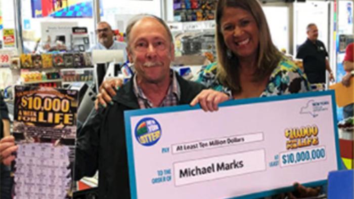 Michael Marks muestra su premio y el juego de raspadito ganador.