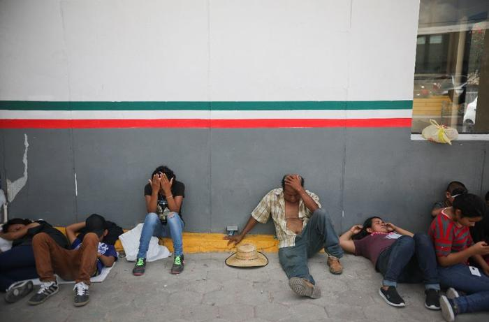 Migrantes descansan cerca de un centro de inmigración mexicano en Matamoros donde la gente ha establecido un campamento para dormir, en la frontera con Brownsville, Texas.