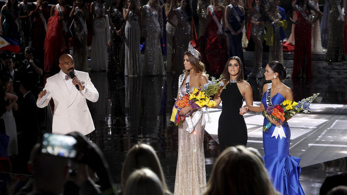 Host Steve Harvey speaks as Miss Colombia Gutierrez, Miss Universe 2014 Vega and Miss Philippines Wurtzbach listen onstage during the 2015 Miss Universe Pageant in Las Vegas