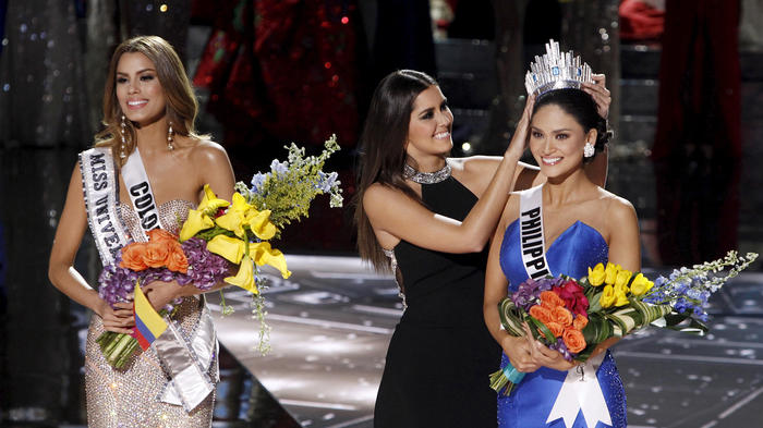 Miss Colombia Gutierrez stands by as Miss Universe 2014 Vega transfers the crown to winner Miss Philippines Wurtzbach during the 2015 Miss Universe Pageant in Las Vegas