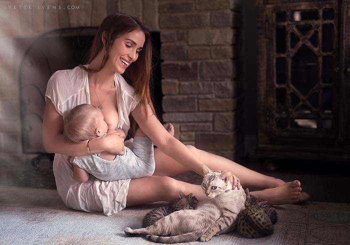 Mujer amamantando un bebé y tocando gatos