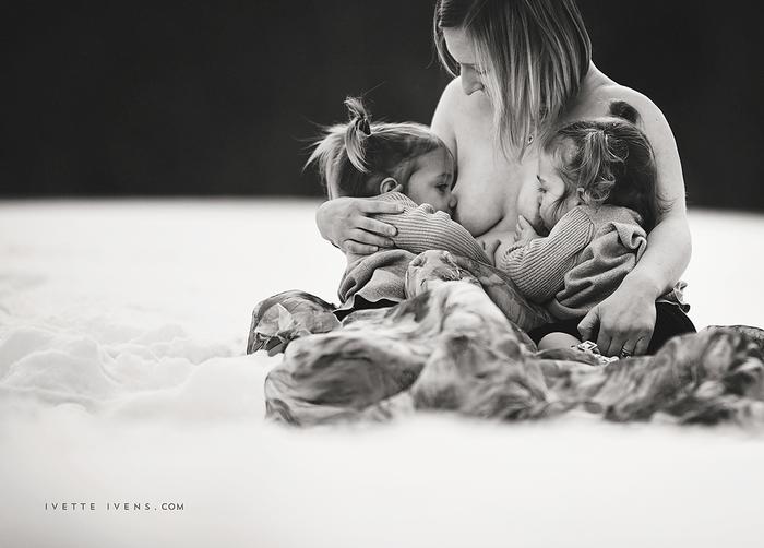 Mujer amamantando a dos niñas