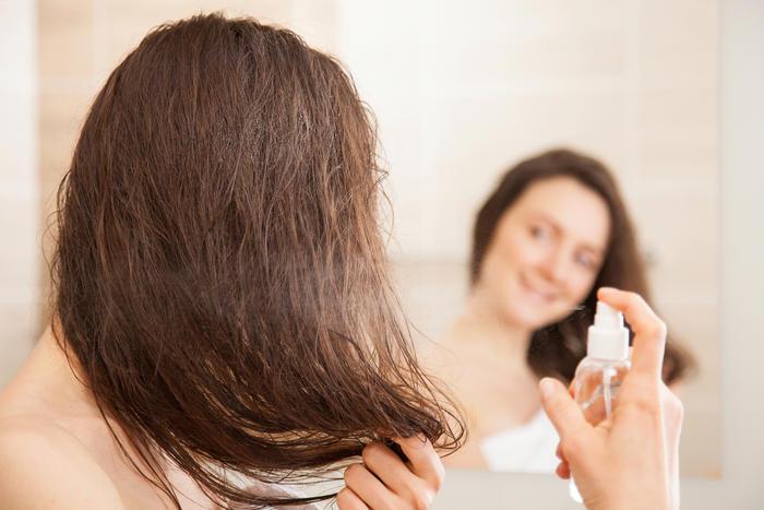 Mujer aplicándose spray en el cabello frente al espejo