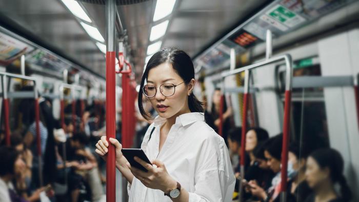 Mujer china con celular en el metro