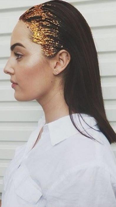 mujer con brillantina dorada en su cabello negro