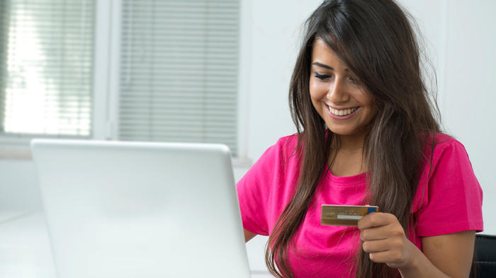 mujer con computadora y tarjeta