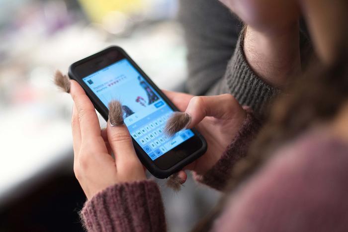 Mujer con uñas peludas sosteniendo un celular