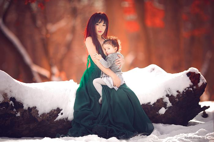 Mujer en vestido verde, amamantando a una niña