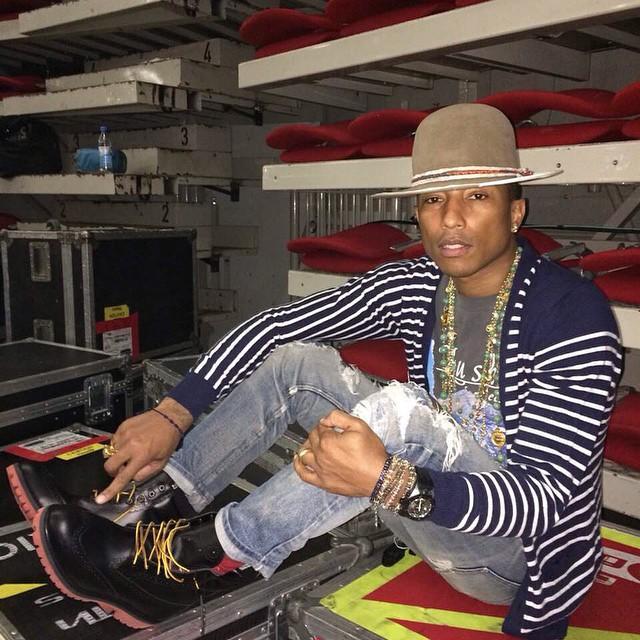 Pharrell con un saco a rayas y sombrero.