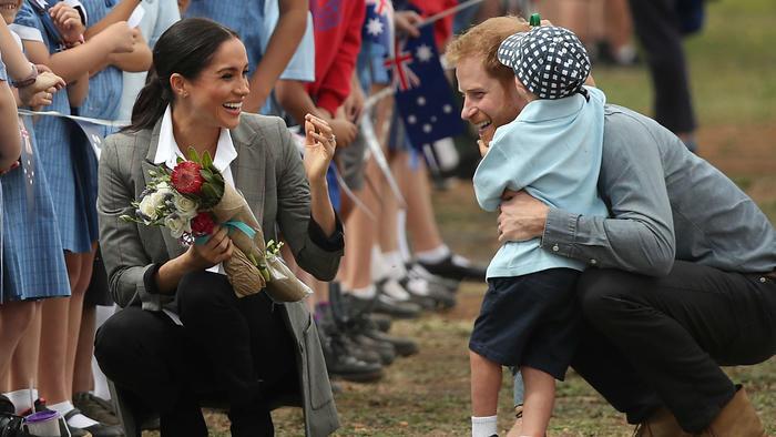 Príncipe Harry y Meghan con un niño