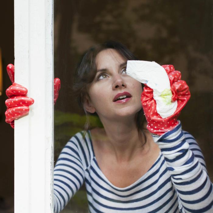 Mujer limpiando ventana de vidrio