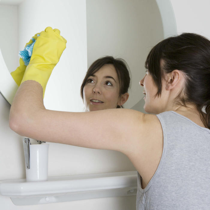 Mujer limpiando espejo