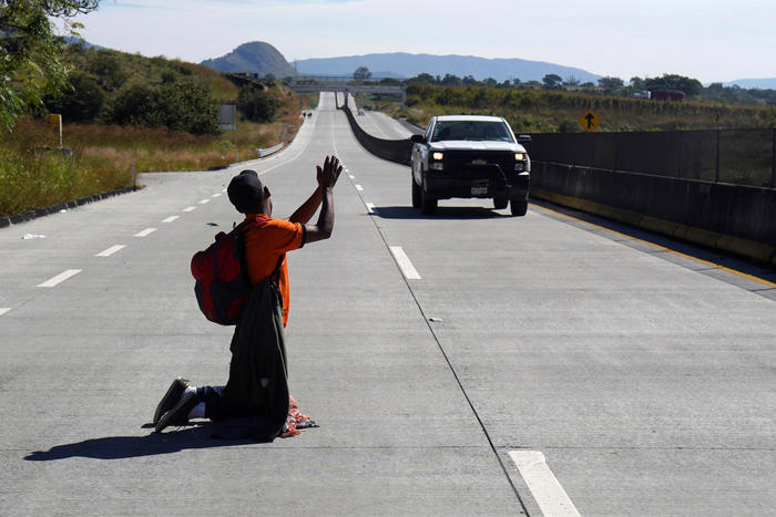A migrant, part of a caravan of thousands traveling from Central America en route to the United States, attempts to hitchhike on the motorway on the outskirts of Guadalajara