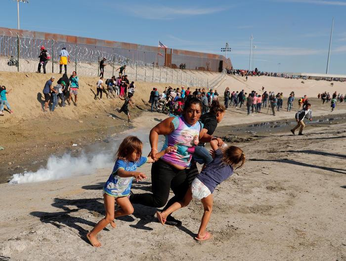 A family runs away from tear gas in front of the border wall between the U.S. and Mexico, in Tijuana