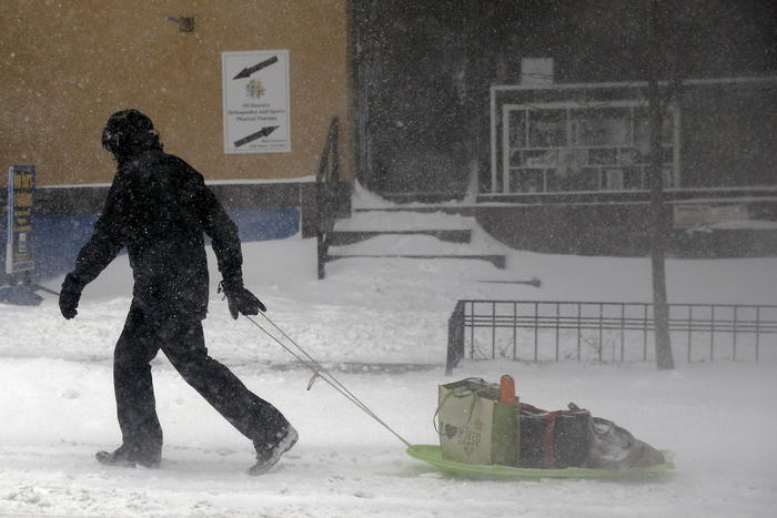A man pulls a sled of groceries through the blowing snow in New York