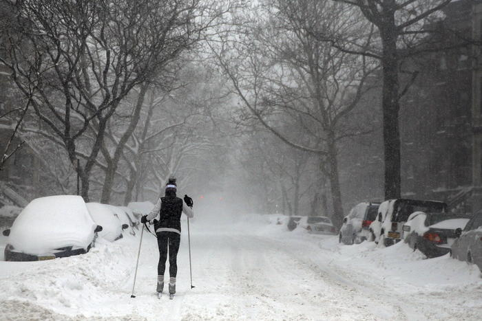 A woman skis in the street through the blowing snow in New York