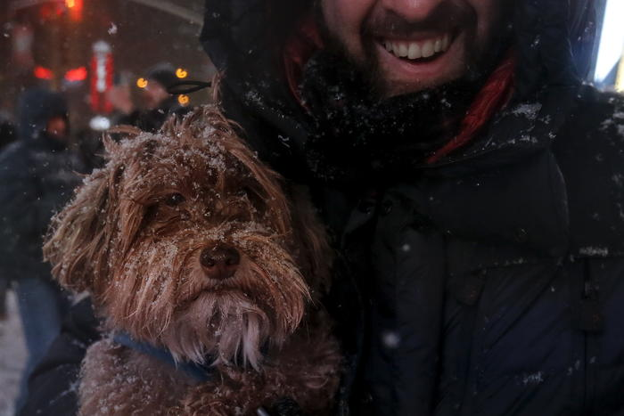A man holds his dog during a snow storm in Times Square in the Manhattan borough of New York