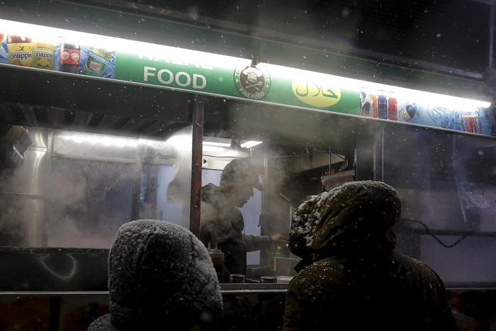 People wait for food they have ordered from a food cart during a snow storm in Times Square in the Manhattan borough of New York