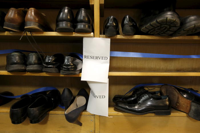 """Shoes removed by visitors out of reverence sit on a shelf marked """"reserved"""" prior to remarks by Obama at the Islamic Society of Baltimore mosque in Catonsville, Maryland"""