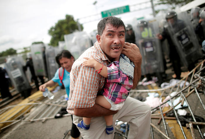 A Honduran migrant protects his child after fellow migrants, part of a caravan trying to reach the U.S., stormed a border checkpoint in Guatemala, in Ciudad Hidalgo