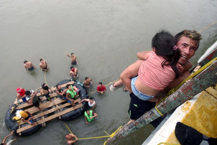 Un migrante sostiene en sus brazos a una niña momentos antes de saltar del puente que conecta a México y Guatemala.