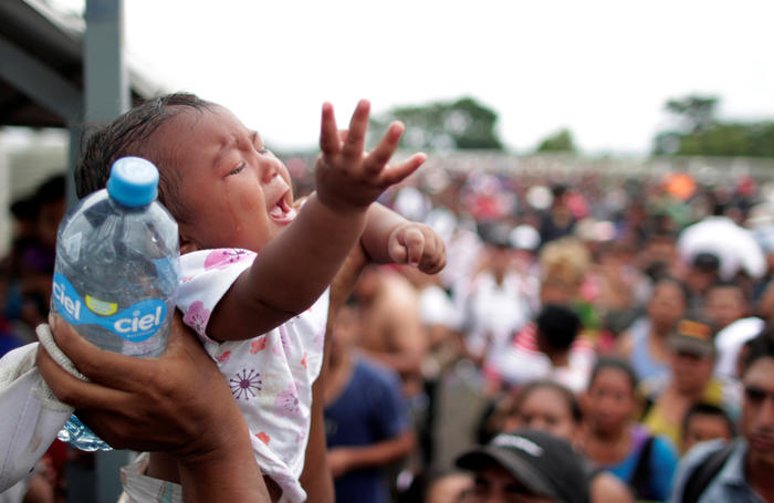 Un bebé llora mientras que los adultos que lo acompañan esperan en la ciudad de HIdalgo, en México, para pedir asilo.