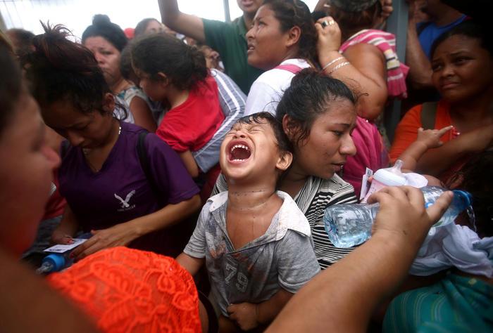 Este niño llora visiblemente angustiado mientras que espera junto a unos adultos en Ciudad Hidalgo para pdeir asilo en México.