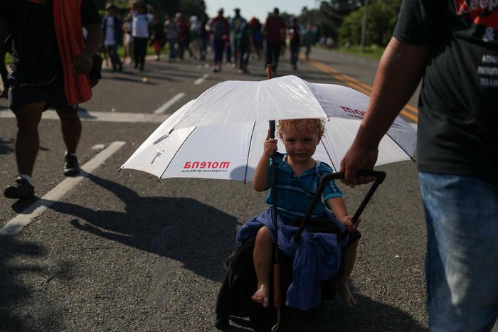 Una niña es llevada encima de una maleta por un aadulto que camina junto a la caravana migrante en su paso hacia Estados Unidos.