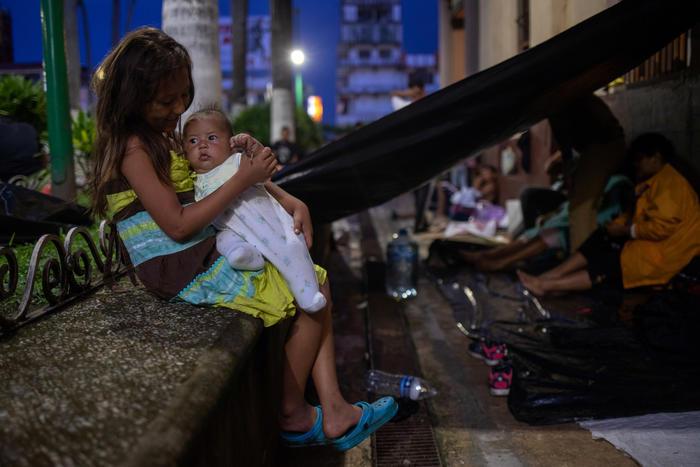 Una niña sujeta en brazos a su hermana mientras que la caravana migrante toma un descanso en Tapachula, México.