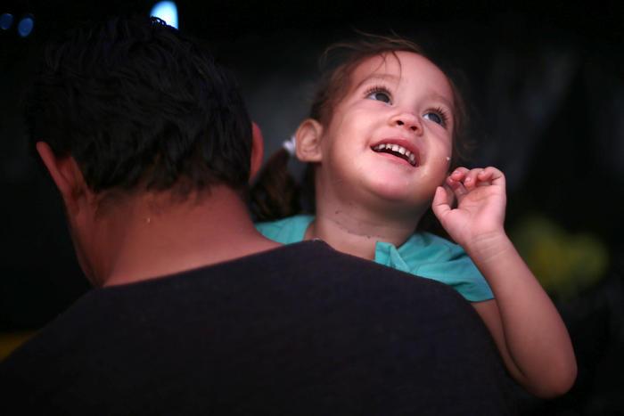 Una niña y su padre caminan junto a la caravana migrante con el objetivo de llegar a suelo estadounidense.