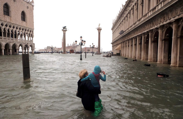 A woman holds a child as she walks in a flooded Saint Mark Square during a period of seasonal high water in Venice