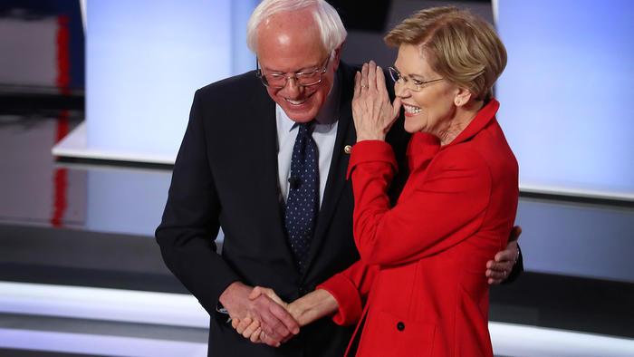 Los candidatos presidenciales demócratas, el senador Bernie Sanders y la senadora Elizabeth Warren, se saludan al comienzo del debate presidencial demócrata en julio de 2019 en Detroit, Michigan.