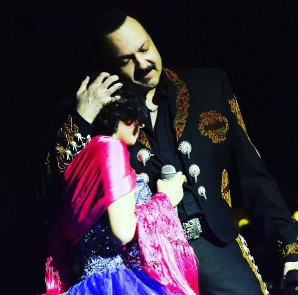 Pepe Aguilar abraza a su hija Ángela Aguilar en el escenario