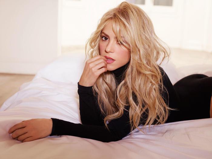 Shakira acostada en una cama