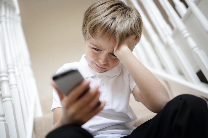 Niño sentado en las escaleras viendo un celular