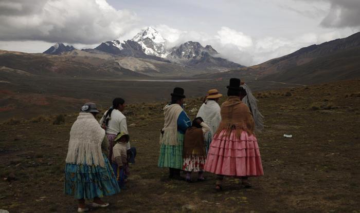 mujeres indígenas aymara mirando la montaña Huayna