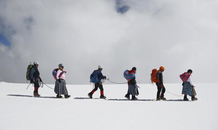 varias mujeres indígenas aymara descendiendo la montaña Huayna Potosí con sus maridos