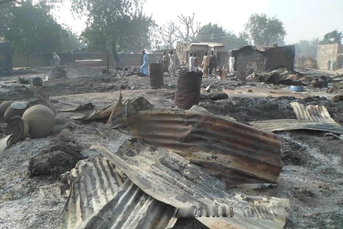 Varias personas caminan entre viviendas quemadas luego de un ataque de extremistas de Boko Haram en al pueblo de Dalori, a 5 kilómetros (3 millas) de Maiduguri, Nigeria, el domingo 31 de enero de 2016. (Foto AP/Jossy Ola)