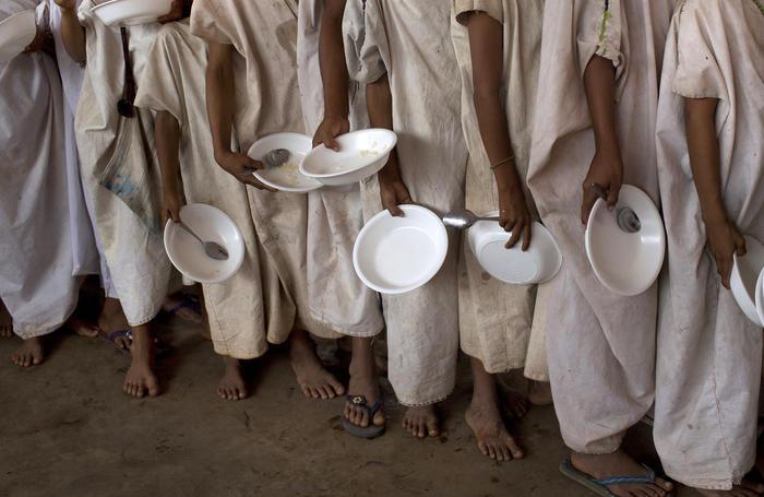 estudiantes con cuencos y cucharas hacen fila para recibir un desayuno gratis