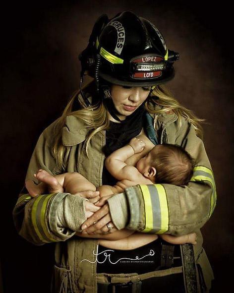 Mujer bombero uniformada amamantando a su bebé