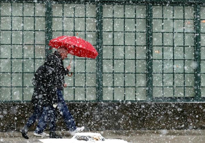 La gente camina en la acera durante un día nevado, el domingo 14 de abril de 2019, en Chicago.
